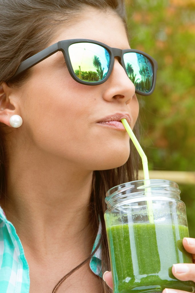 Woman with sunglasses drinking green vegetable smoothie outdoors