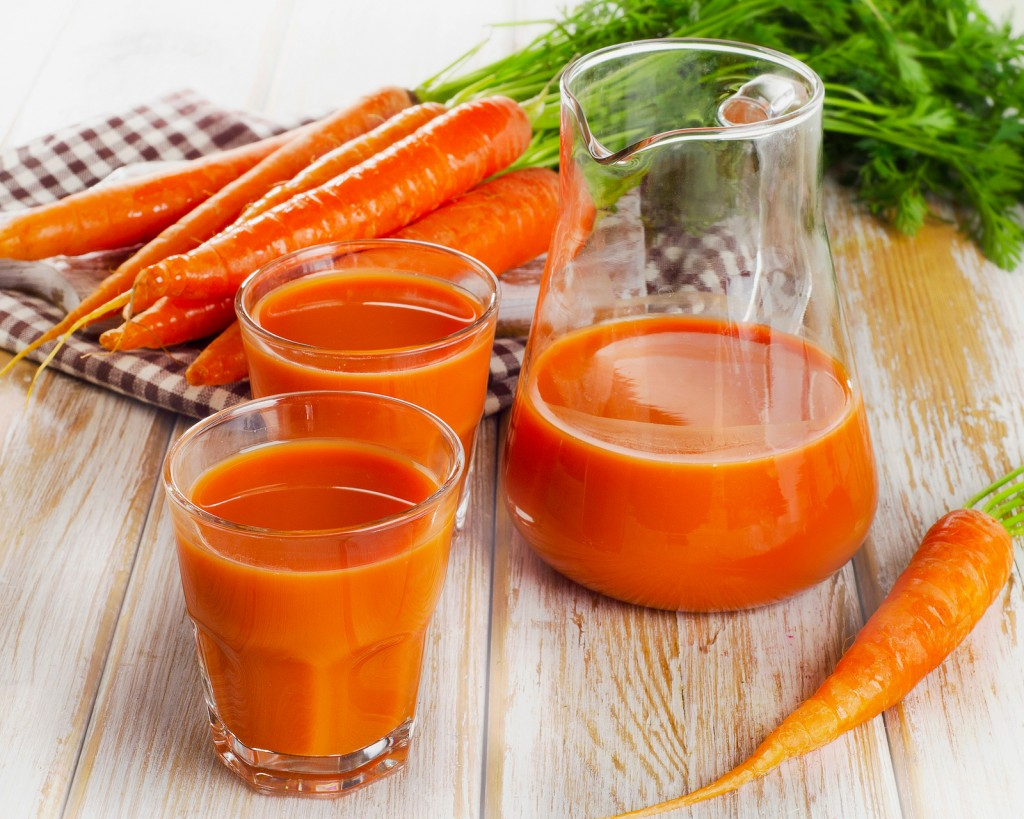 Fresh Carrot Juice And Organic Raw Carrots On A Wooden Table.