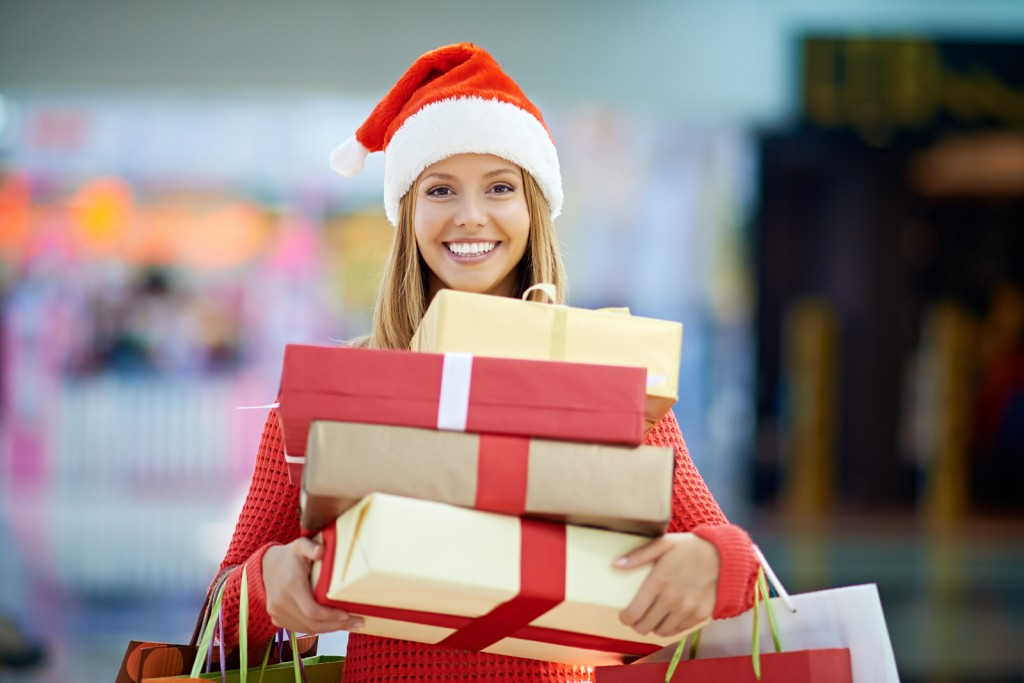 Portrait of a young woman holding gift boxes