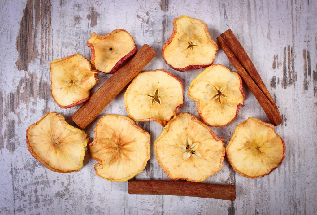 Slices Of Dried Apple And Cinnamon Sticks On Old Rustic Wooden B