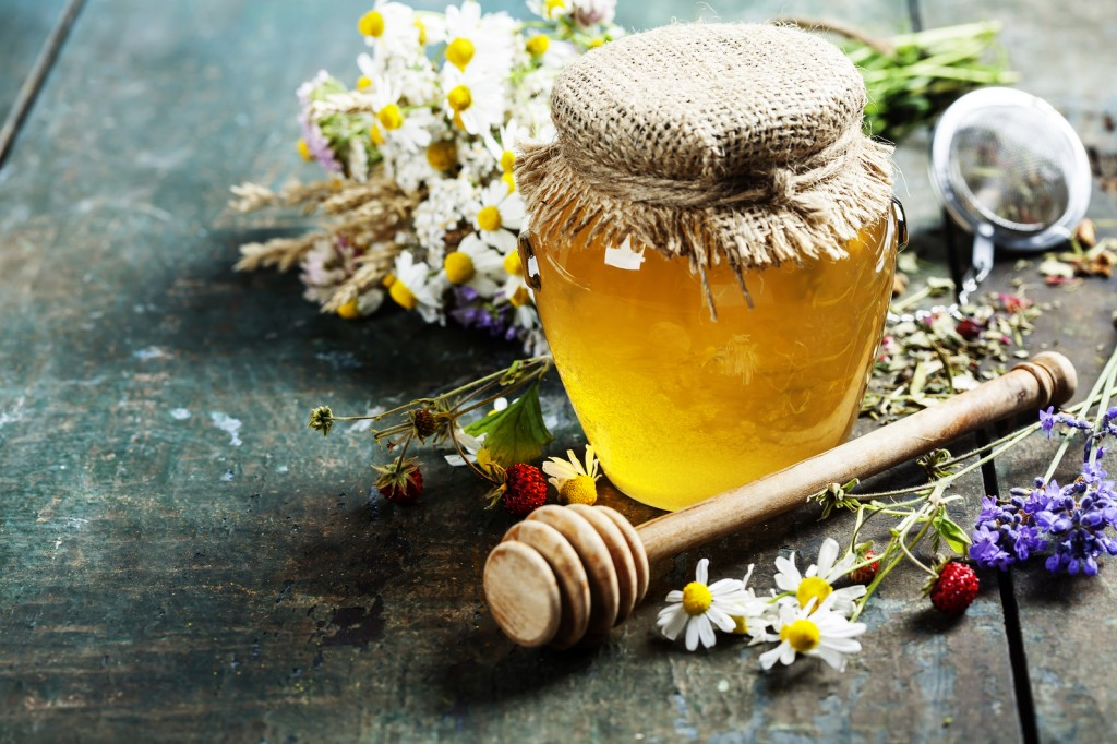 Honey and Herbal tea on wooden background - summer, health and o